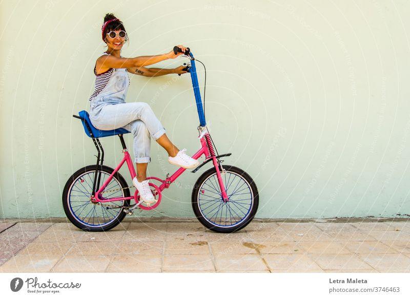 Young urban girl in a bike in summer time Young woman citygirl urban scene street scene colorful bike Bicycle bike girl biker urban bicycle happy girl pink bike