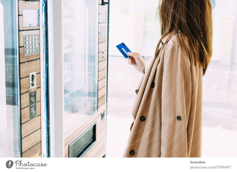 woman uses her credit card to pay at the vending machine tourist traveling voyage economy virus coronavirus epidemic pandemic mask protection outbreak infection
