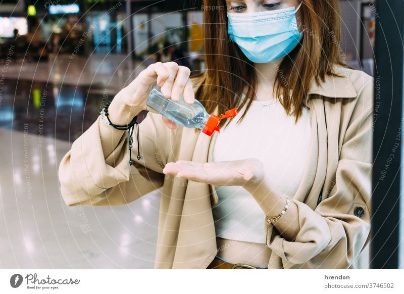 a woman wearing a face mask and using hydro-alcoholic gel to disinfect her hands at the train station traveling voyage virus coronavirus epidemic pandemic
