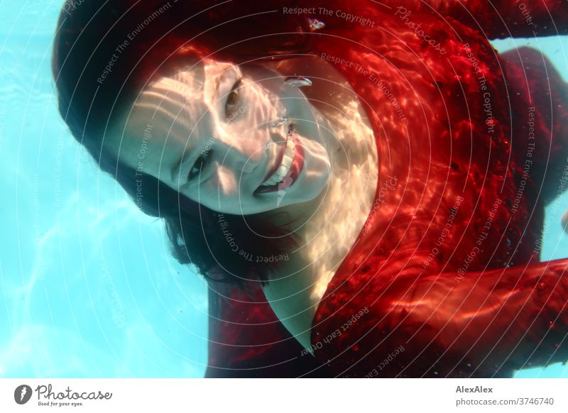 Underwater portrait of a young woman in a red dress girl Young woman Woman 18-25 years already Athletic smile Laughter Red-haired Dark-haired fit Dive be afloat