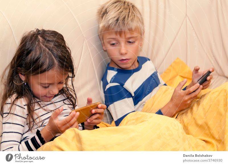 Little girl and boy playing game or watching something on mobile smart phone cartoons mobile phone resting watching cartoons surfing the net connection