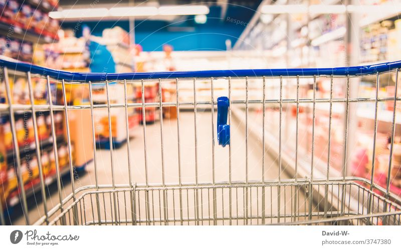 Shopping trolleys in the supermarket between shelves with food Shopping Trolley Food Supermarket business Customer consumer Store premises void Empty