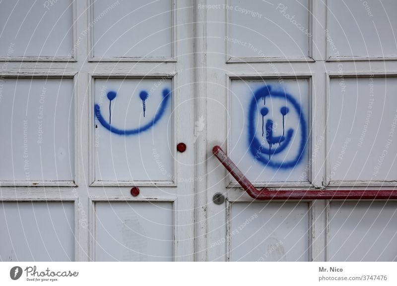 Smileys left and right door Entrance Front door White Blue Daub door handle smile Good mood Closed Door handle Wooden door Old Lock Happiness Round Way out