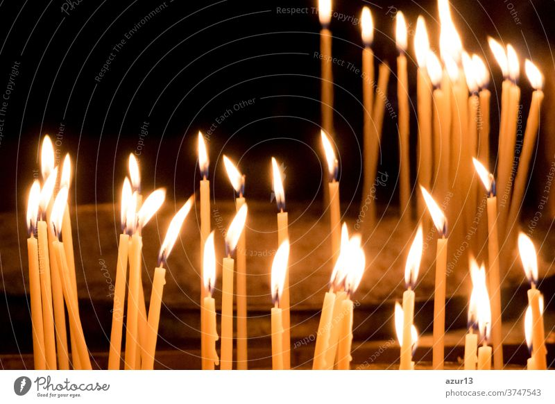 Group of yellow candles in church for faith resurrection prayer. Candlelight fire flames in circle rows are religion symbol for peace, life and soul silence. Obituary hope sacrifice against sorrows