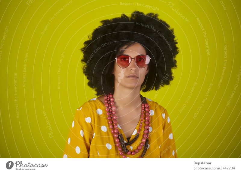 Portrait of Indian girl with the curly hair on yellow background funny afro hairstyle vintage portrait retro colorful colors rap trap glasses seventy people