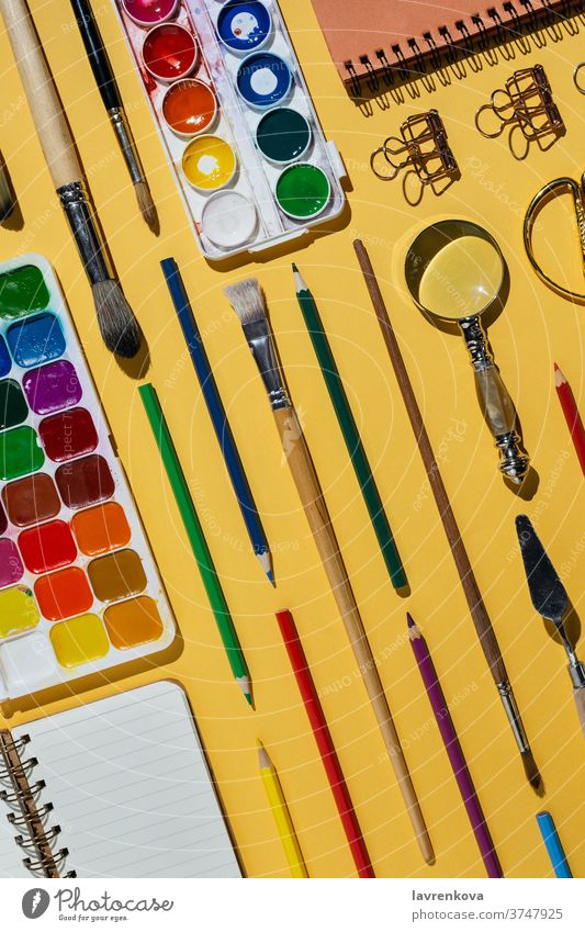 Flatlay of watercolors, brushes, notebooks and other stationery and art supplies on yellow blank business colorful creative designer desk drawing education