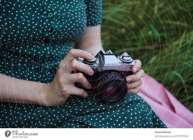 Closeup of woman's hands holding film vintage camera closeup female faceless photographer professional dress pictures outdoors grass