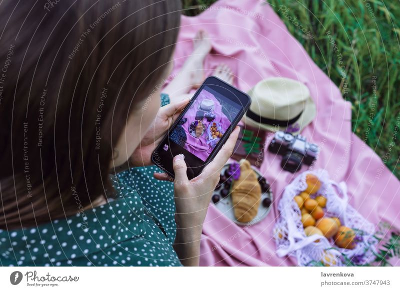 Female taking picture of picnic on green grass outdoors communication smartphone female social media post food blanket pink selfie camera croissant pastry
