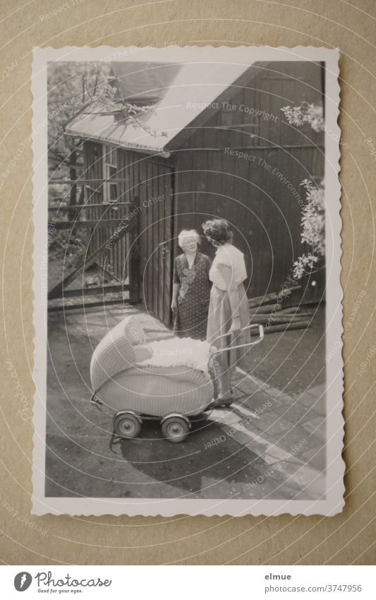 Memories of the 1960s - black-and-white picture with deckle edged paper shows three generations in a front garden / fashionable pram and mother talking to grandmother