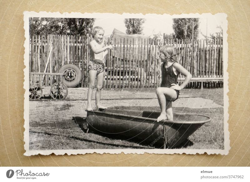 Memories of the 1960s - a black and white photo print with a deckle edge lies on beige paper and shows two girls bathing in an old zinc bathtub in a rural environment with a fence, handcart and car tire