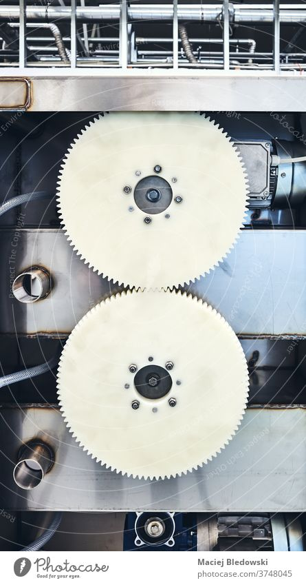 Two plastic meshing gears transmitting rotational motion of a machine. equipment technology industry factory manufacturing production industrial engineering