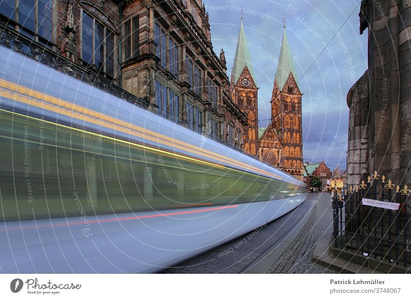 Tram in Bremen City hall Church Church towers Town Street Light Architecture Manmade structures urban Europe Old Dusk St. Petri cathedrale swift Speed tempo