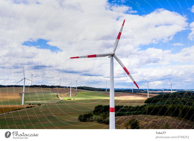 some wind wheels in the countryside mid air from above wind wheels from above wind turbine wind turbines cloudy sky clouds green energy wind energy electricity
