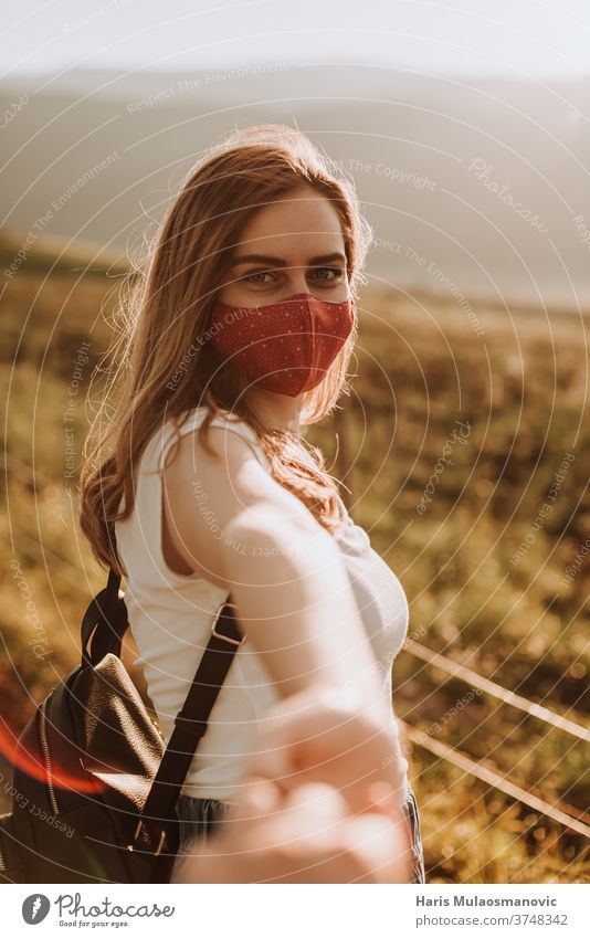 Young woman with mask going to adventure holding hand of her boyfriend attractive backpack beautiful beautiful landscapes beautiful woman beauty caucasian