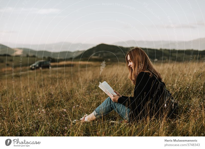 Young beautiful blonde hair woman solo traveler reading a book in nature alone away from the city beauty concept countryside escape from city feeling female