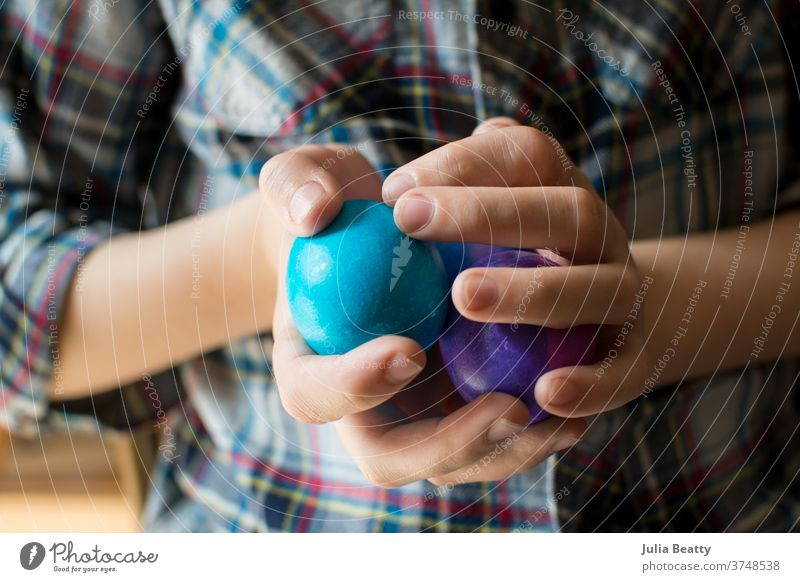 Child wearing plaid shirt holding multicolored Easter Eggs Easter egg Spring Decoration Multicoloured Feasts & Celebrations Tradition hands eggs fingernails