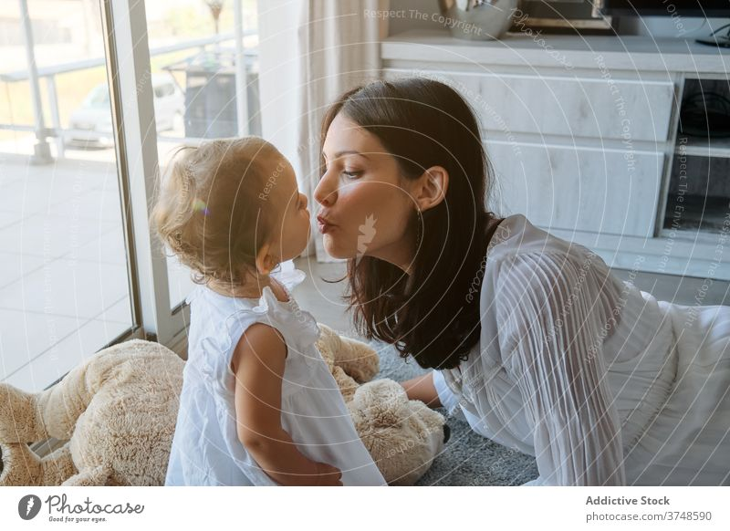 Woman lying on the floor kissing a toddler at home loving innocence tenderness affectionate parenting mum touching feeling infant motherhood togetherness