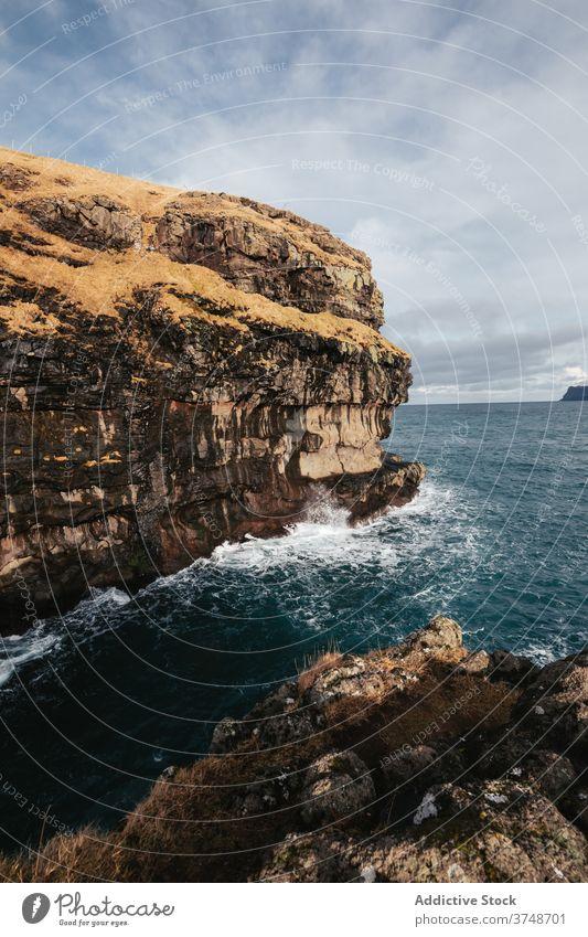 Rocky cliff near sea on Faroe Islands rock seascape winter season cold steep terrain faroe islands rocky scenery majestic coast shore water sky calm overcast