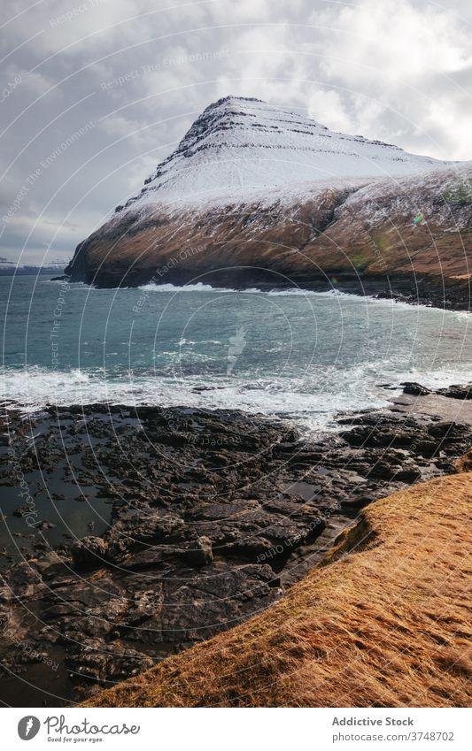 Rocky cliff near sea on Faroe Islands rock seascape winter snow season cold steep terrain faroe islands rocky scenery majestic coast shore water sky calm