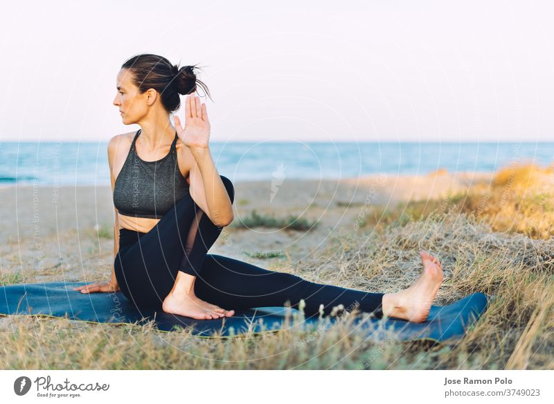 young woman doing yoga exercise on the ground outdoors by the sea people healthy lifestyle balance exercising lifestyles one person sunlight horizontal vitality