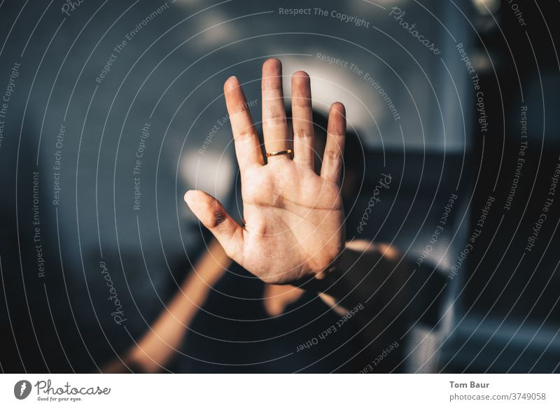 Stop! woman holds her hand, palm out, with a stop gesture upwards, on the middle finger a golden ring by hand Gestures Palm of the hand Colour photo Woman
