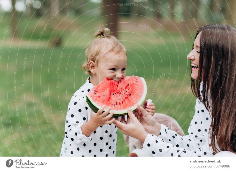 happy mother and daughter eat watermelon in summer park. Happy smiling family eating watermelon in park. Mother and daughter spend time together. Diet, vitamins, healthy food concept. selective focus