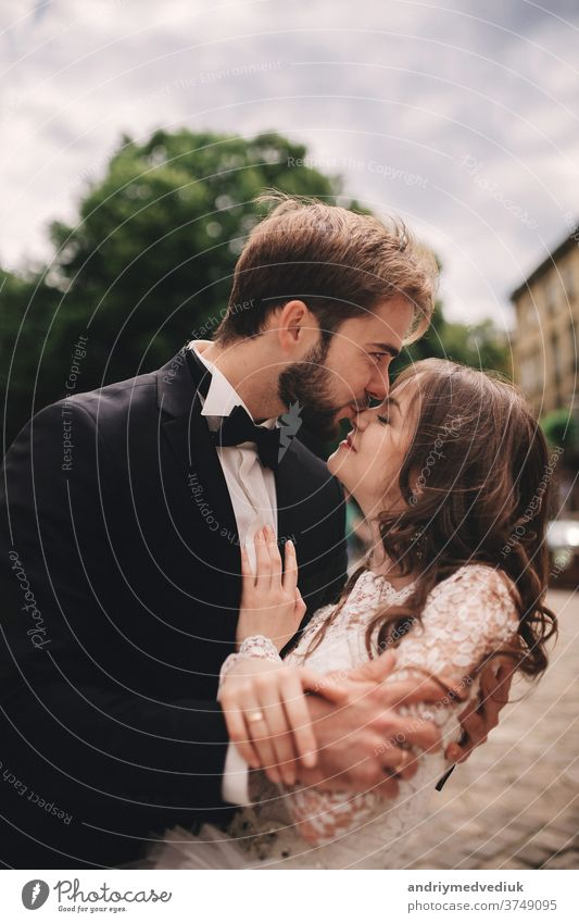 Happy newlywed couple hugging and kissing in old European town street, gorgeous bride in white wedding dress together with handsome groom. wedding day european