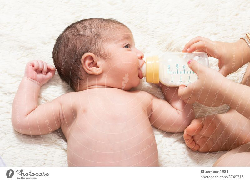 Young sister feeding little newborn brother by milk bottle on bed Caucasian face nutrition eating holding girl happy adorable help baby backdrop beautiful care