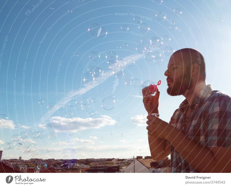 Man blowing soap bubbles from his balcony. Exit restriction quarantine due to coronavirus, home office and social media concept man terrace exit covid19