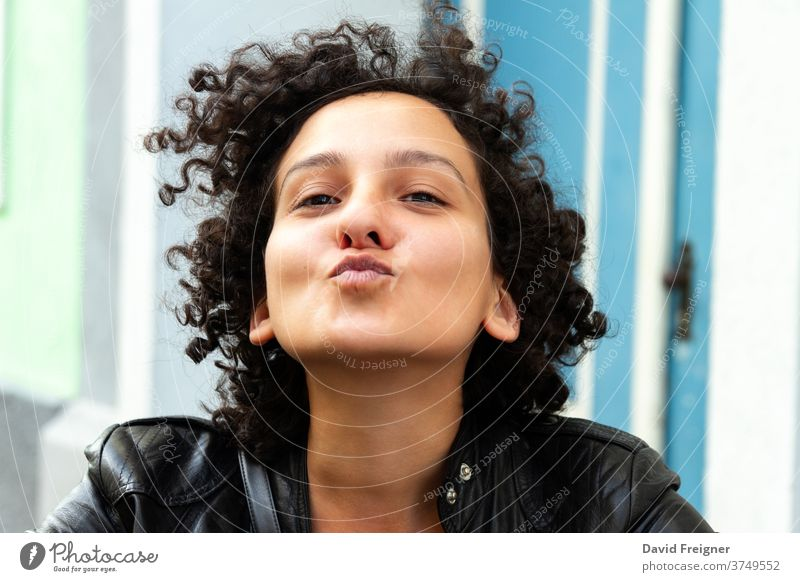 Young attractive woman with curly hair gesturing for a camera selfie and sending kisses. Urban city people concept. young fun cheerful face happy positive
