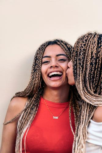 Lovely African American Sisters kiss giving a kiss sisters african girls front view looking at camera siblings braids african american street attractive young