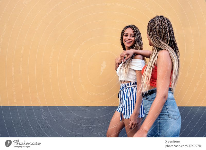 Cool Sisters Having Fun side view sisters walking street braids ethnic racial looking at each other smiling urban women portrait two women background city