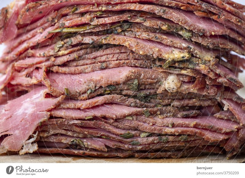 Stack of sliced pastrami meat Beef brisket Rustic slices Slice stacked Meat Close-up Red deli cut chill Folded Thin roasted Eating seethed Delicacies Frying