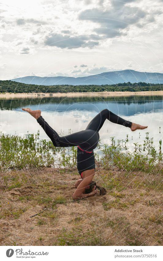 Woman practicing headstand yoga pose near lake woman practice sirsasana balance inversion variation advanced harmony wellness lifestyle female flexible