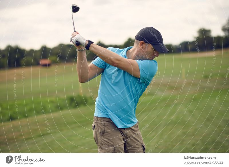 Man playing golf swinging at the ball as he plays his shot using a driver viewed from behind looking down the fairway in a healthy active lifestyle concept man