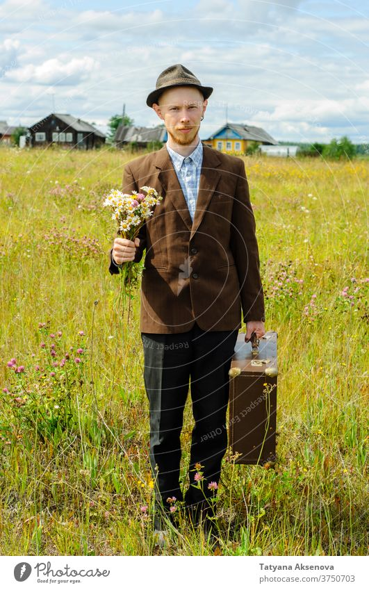 Man hipster with old retro suitcase and wildflowers bouquet man countryside cottagecore vintage summer brown field green jacket rustic travel young male