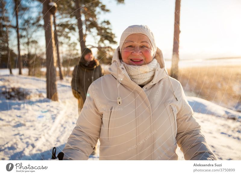 Winter sport in Finland - nordic walking. Senior woman and man hiking in cold forest. Active people outdoors. Scenic peaceful Finnish landscape. senior winter