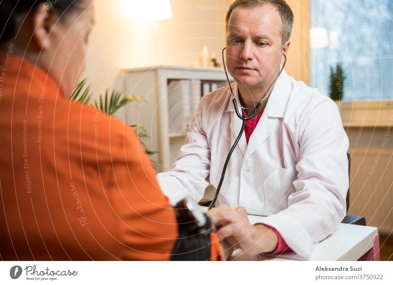 Doctor measuring blood pressure of female patient in hospital office. Sick senior woman having a doctor appointment. Close up care support old people hand