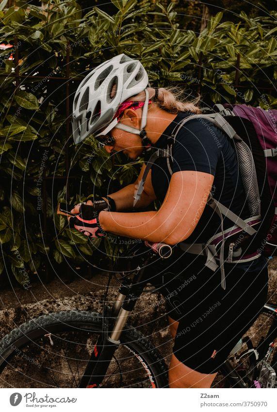 Cyclist on a bike tour looks for the way on her smartphone Mountain bike Nature Landscape Bavaria Helmet Sunglasses sportswear Jersey rest Break Trip Braids