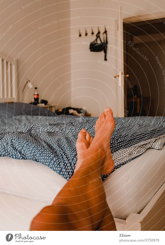 Young man relaxes in the bedroom Bed at home Relaxation relaxation dwell Cozy Old building Lie rest Write Weekend free time Bedroom Morning Lifestyle Legs feet