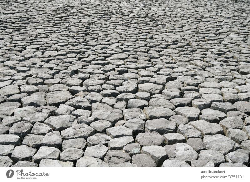 cobblestone background with uneven natural stone pattern rock texture paving surface pavement gray abstract backdrop cobbled rocks blocks nobody perspective