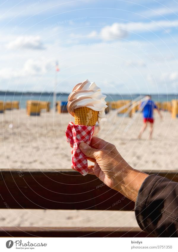A hand holds an ice cream waffle with soft ice cream. blurred background with beach, beach chairs, sea and a person. nice weather with sunshine. Blue sky, clouds