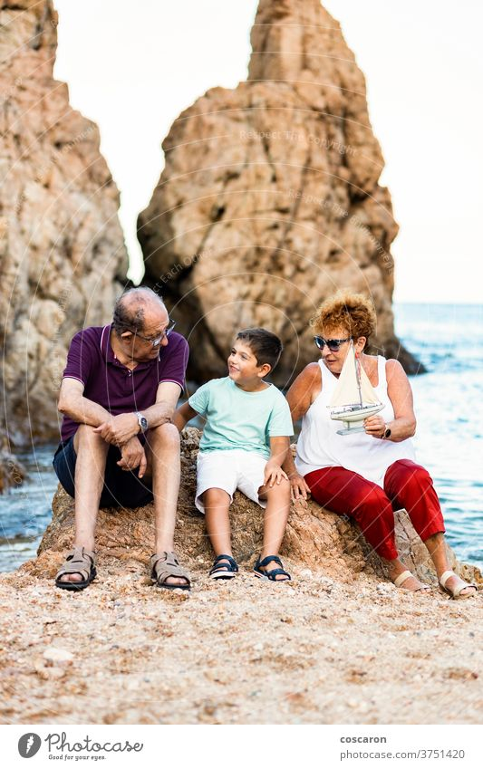 Grandparents and grandson playing with a toy sailboat on the beach boy caucasian child childhood coast coastline cute family grandfather grandmother grandpa