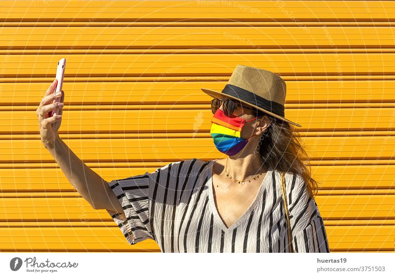 Middle-aged woman wearing a rainbow-colored protective mask. LGTB.Covid-19 concept lgbt flag coronavirus people lifestyle transgender community lesbian pride