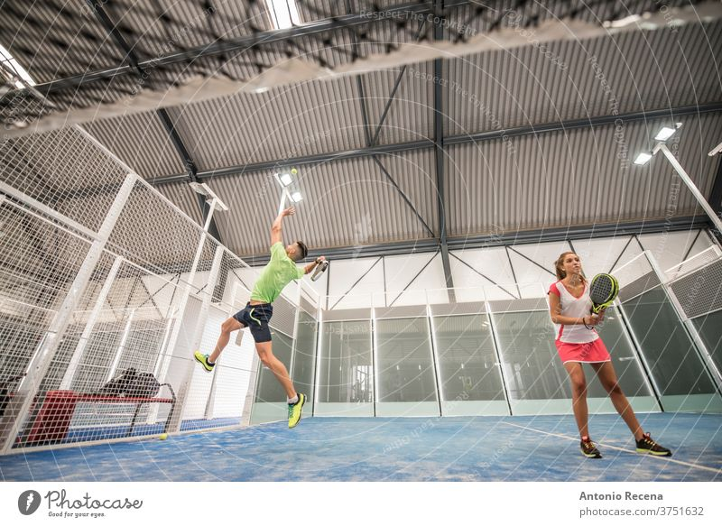 paddle tennis indoors training. Wide angle view under the net padel pádel sport sports recreation class court man woman women blue lifestyles shot couple ball