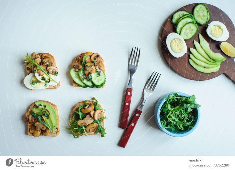 various morning vegetarian toast set with mushrooms, avocado, arugula, cucumber and eggs. Healthy food on white background bread vegetable sandwich breakfast