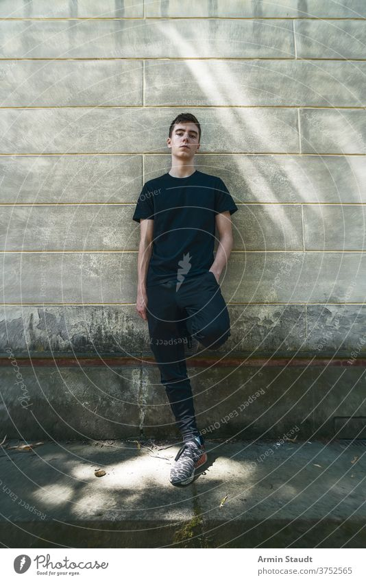 portrait of a cool, standing young man who is leaning against a wall grunge confident serious sportswear dirt outdoor teenager looking male beautiful casual