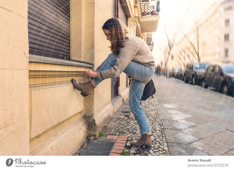 young woman ties her shoe on the street portrait outdoor pavement cars city town urban crouching shoes summer beautiful concentrated bag wall brick Berlin