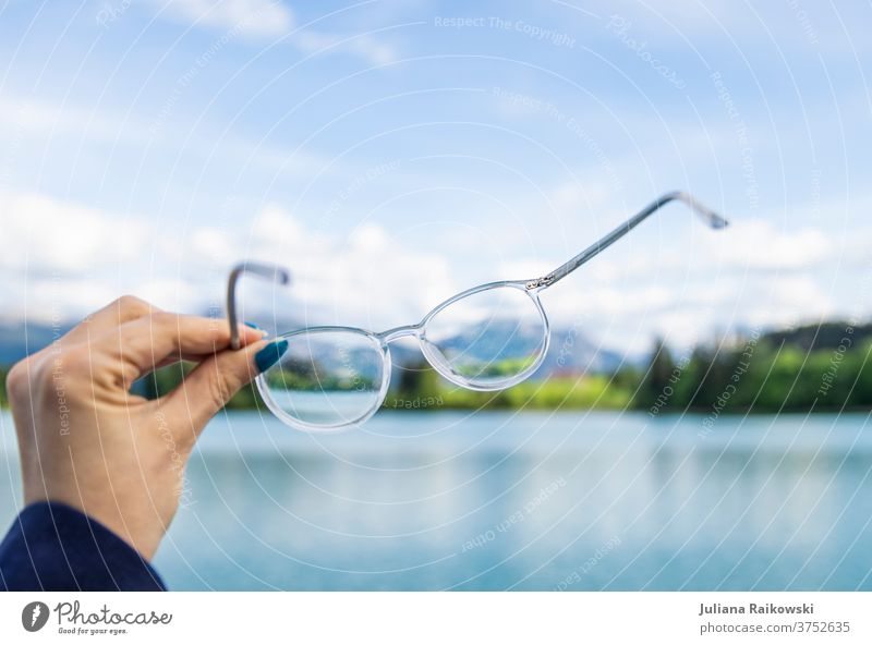 Glasses in front of beautiful nature Eyeglasses Nature nearsighted Looking Eyes Vision Person wearing glasses Optician Opthalmology Healthy Colour photo Optics