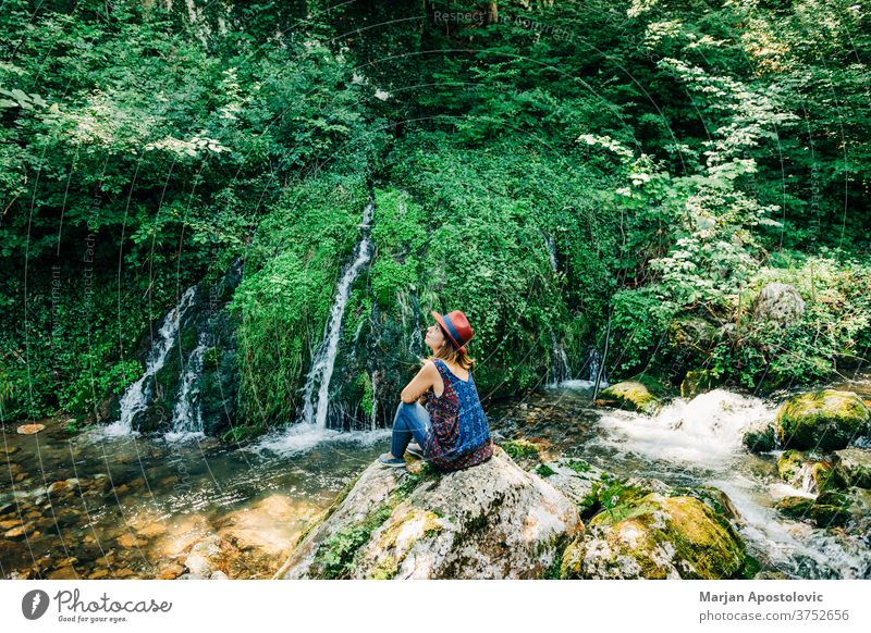 Young female nature explorer enjoying by the waterfalls adventure beautiful cascade casual caucasian discover discovery flow flowing forest fresh girl green